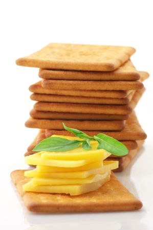 Stack of square crackers with slices of cheese and basil isolated on white background. photo