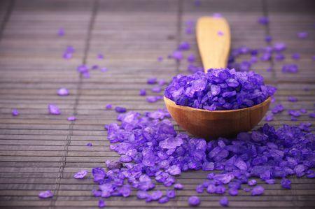 gezondheid: Violet bad zout in houten lepel op bruine mat.