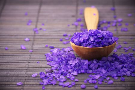 Violet bath salt in wooden spoon on brown mat.