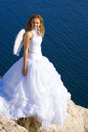 Beautiful bride in image of angel standing on rock over blue sea. photo