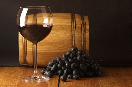 rustic food: Glass of red wine, dark grape and souvenir barrel on wooden surface.