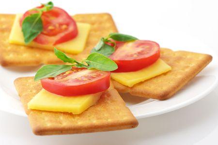 Tres cuadrados galletas con rodajas de queso, tomate y albahaca en plato blanco sobre fondo blanco.