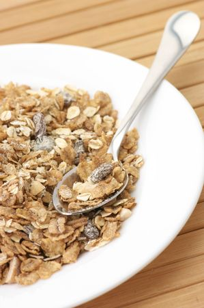 Heap of muesli in white plate with spoon on wooden surface. photo