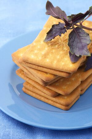 Stack of square crackers with purple basil in blue plate on blue linen cloth. photo