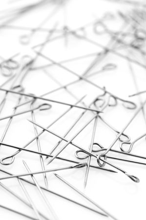 placer: Placer of steel sewing pins on white background. Stock Photo