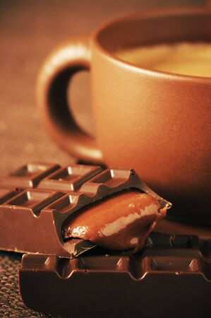 Brown ceramic cup of coffee and broken chocolate bar with caramel stuffing close-up on brown canvas. photo