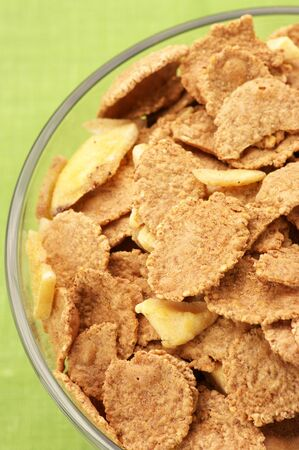 roughage: Close-up of glass bowl with breakfast cereal on green background.