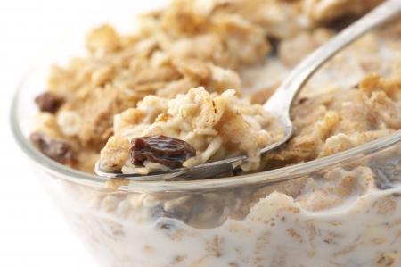 oatmeal: Primer plano de muesli en cuchara en Bol de cristal de muesli con leche.  Foto de archivo
