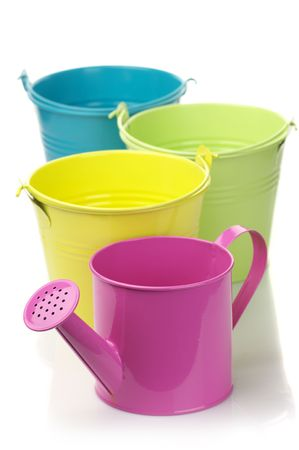 Three colorful buckets and watering can isolated on white background. photo