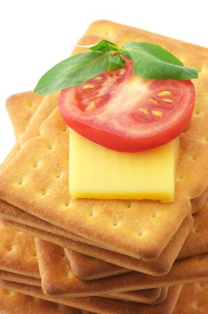 Stack of square crackers with slices of cheese, tomato and basil close-up on white background. photo