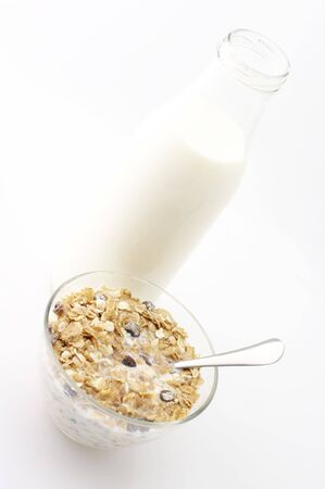 Muesli with milk in glass bowl and bottle of milk on white background. photo