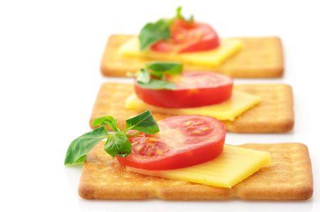 crackers: Tres cuadrados galletas con rodajas de queso, tomate y albahaca aislados sobre fondo blanco.