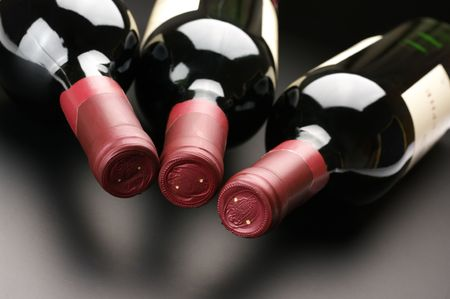 Three closed red wine bottles lying on dark background.