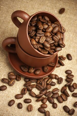 Two brown ceramic cups with roasted coffee beans on canvas. Stock Photo - 7749285