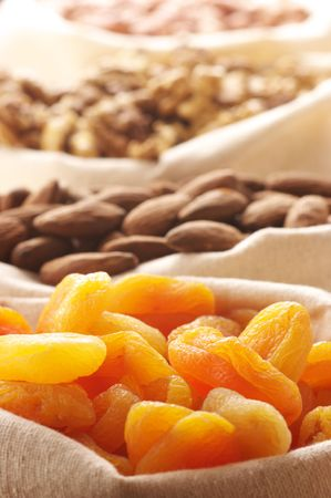 apricot kernels: Heap of nuts and dried apricots in canvas bags. Focus on apricots.