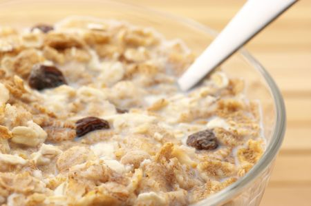 Close-up of muesli with milk in glass bowl and spoon on wooden surface. photo