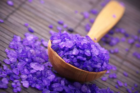 bath salt: Close-up of violet bath salt in wooden spoon on brown mat. Stock Photo