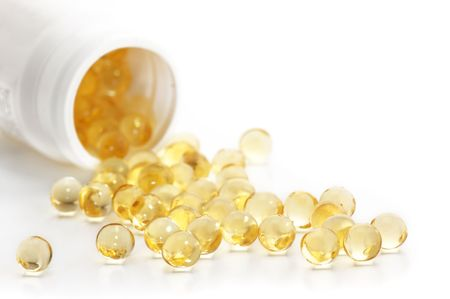 vitamins pills: Capsules of fish oil spilled out open container on white background.  Stock Photo