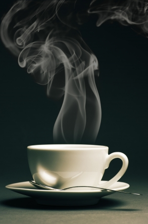 Cup of hot coffee with steam on dark background. Toned image.