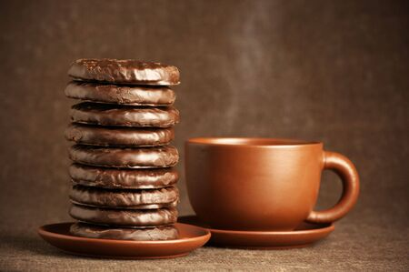 Stack of chocolate cookies and cup of coffee on brown canvas. photo