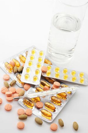 Heap of various pills, thermometer and glass of water on light background. Stock Photo - 7835793