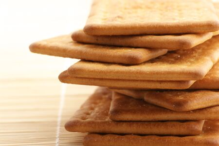 Stack of square crackers close-up on wooden mat. photo