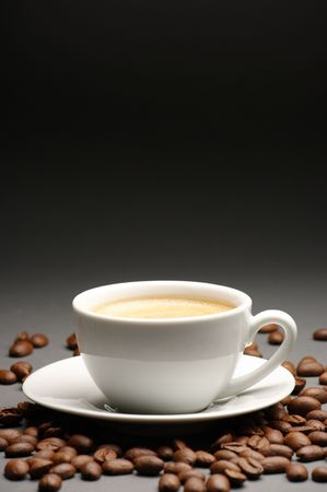froth: White cup of coffee with froth and coffee beans on dark gray background with copy space.