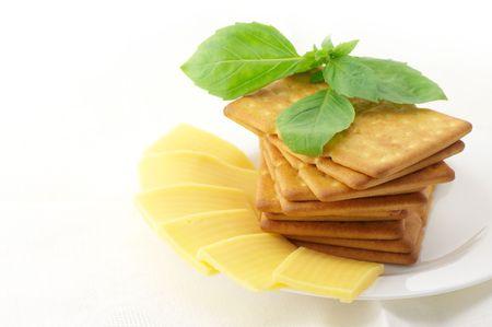 galletas integrales: Pila de galletas cuadradas, rodajas de queso y albahaca en plato blanco sobre fondo blanco.  Foto de archivo