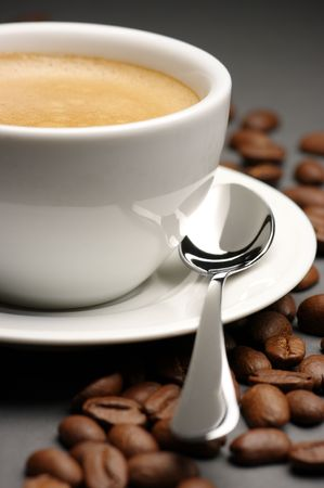 White cup of coffee with froth and coffee beans on dark gray background. Reklamní fotografie