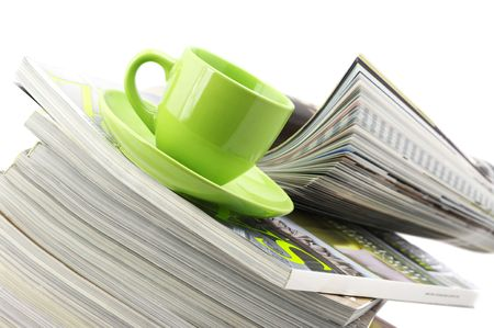 Stack of magazines and green cup of coffee on white background.