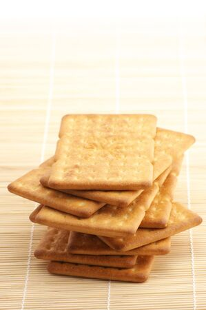 Stack of square crackers on wooden mat. photo