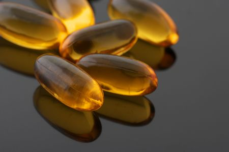 Capsules of cod liver oil on gray background with reflection. photo