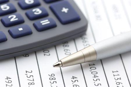 calculadora: Primer plano de la pluma de plata y calculadora en n�meros de tabla de papel.