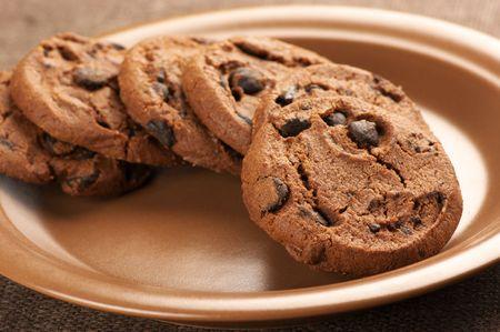 galletas: Galletas de chocolate con chips en placa cerámica marrón.  Foto de archivo