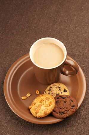 Assorted cookies and brown mug of cappuccino on brown ceramic plate. photo