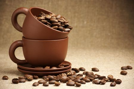 Two brown ceramic cups with roasted coffee beans on canvas. Stock Photo - 8080595
