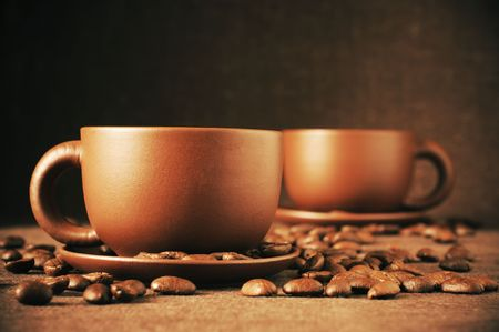 Two brown ceramic cups of coffee and roasted coffee beans on brown canvas. Stock Photo - 8080606