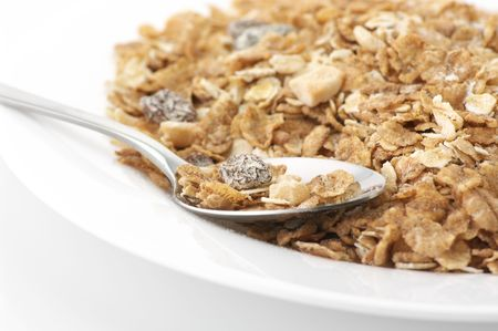 roughage: Heap of muesli in white plate with spoon on white background.