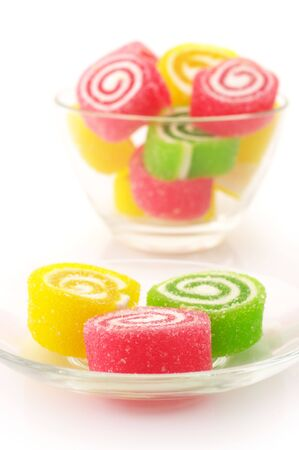 Colorful candy in glass saucer and bowl on white background. photo