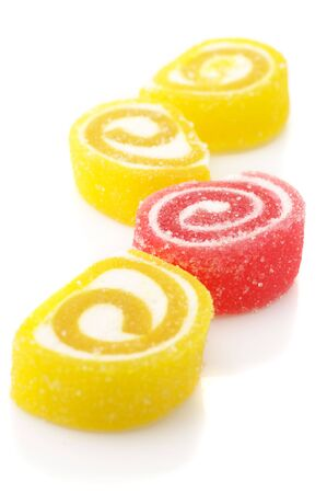 Red and yellow candy isolated on white background. Focus on red candy. photo