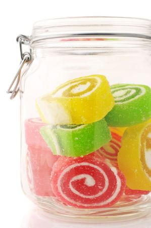 Close-up of colorful candy in glass jar on white background. photo