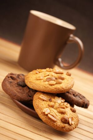 Assorted cookies and brown mug of coffee on wooden mat. photo