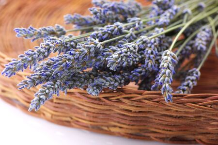Bunch of dried lavender close-up in wicker basket. photo