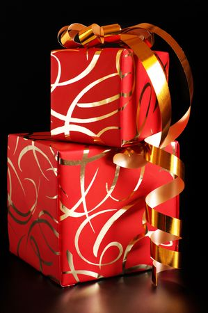 Stack of red gifts with golden ornament on black background. photo