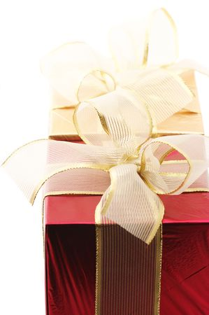 Close-up of red and gold foil gifts with golden bows on white background. photo
