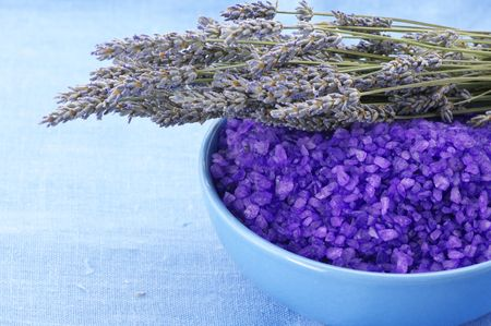 Violet bath salt in blue bowl and bunch of dried lavender on blue linen cloth. Stock Photo