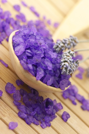 Close-up of violet bath salt in wooden spoon and twigs of lavender on wooden surface. Stock Photo - 8335675