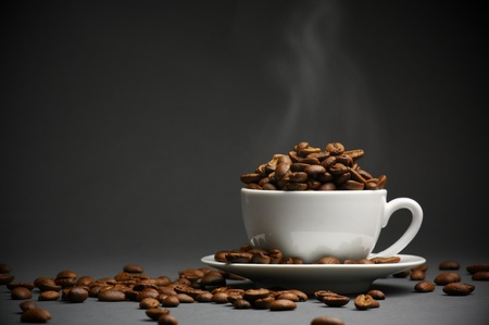 Hot roasted coffee beans in white cup with saucer on dark gray background. Stock Photo