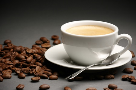 froth: White cup of coffee with froth and coffee beans on dark gray background. Stock Photo