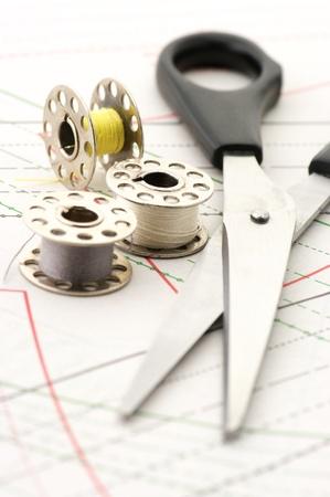 sew: Staal schaar met zwarte hand vat en spoelen van draad op papier naai patroon.